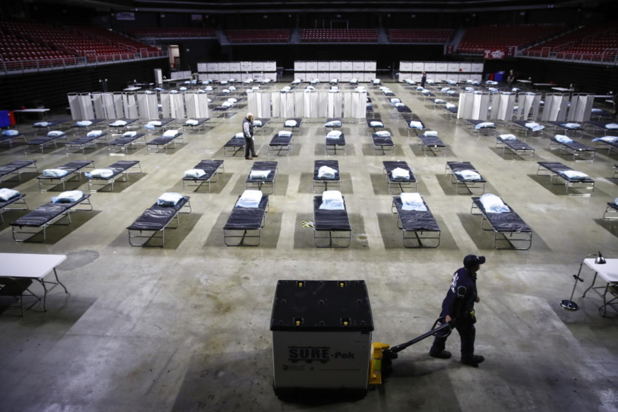 A worker moves items at a Federal Medical Station for hospital surge capacity set up at Temple University's Liacouras Center in Philadelphia, Monday, March 30, 2020.