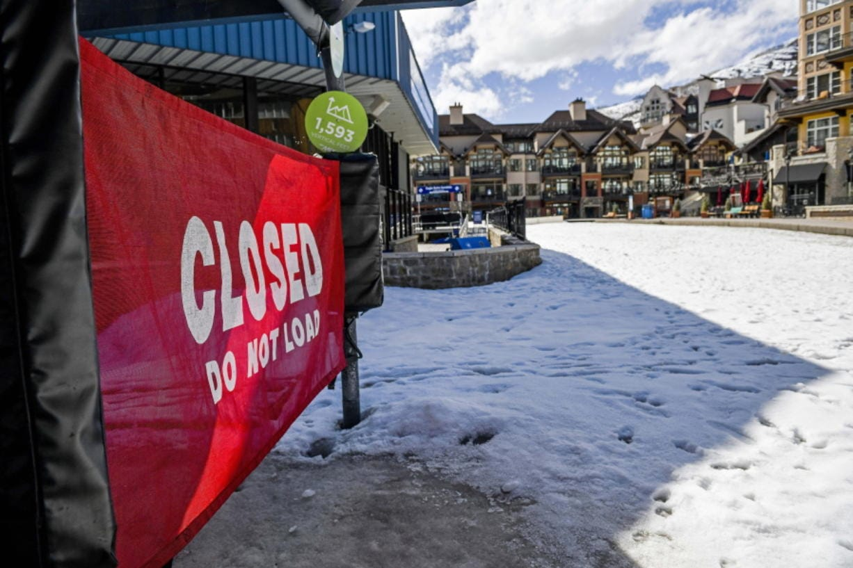 "In this Tuesday, March 24, 2020, photo a sign hangs on a closed ski lift in Vail, Colo., after Vail Ski Resort closed for the season amid the COVID-19 pandemic. Ski resorts across the West that were shut down amid coronavirus fears are grappling with an economic ""body blow"" at a time when they normally would be welcoming hoards of spring break revelers."
