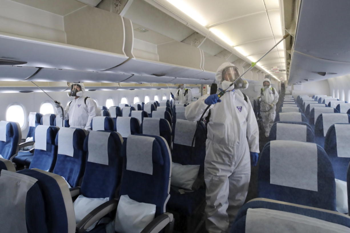 Workers wearing protective gears spray disinfectant inside a plane for New York as a precaution against the new coronavirus at Incheon International Airport in Incheon, South Korea, Wednesday, March 4, 2020. The coronavirus epidemic shifted increasingly westward toward the Middle East, Europe and the United States on Tuesday, with governments taking emergency steps to ease shortages of masks and other supplies for front-line doctors and nurses.