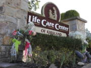 Flowers left next to the sign that marks the entrance to the parking lot of the Life Care Center in Kirkland, Wash. are shown Monday, March 9, 2020, near Seattle. The nursing home is at the center of the outbreak of the COVID-19 coronavirus in Washington state. (AP Photo/Ted S.
