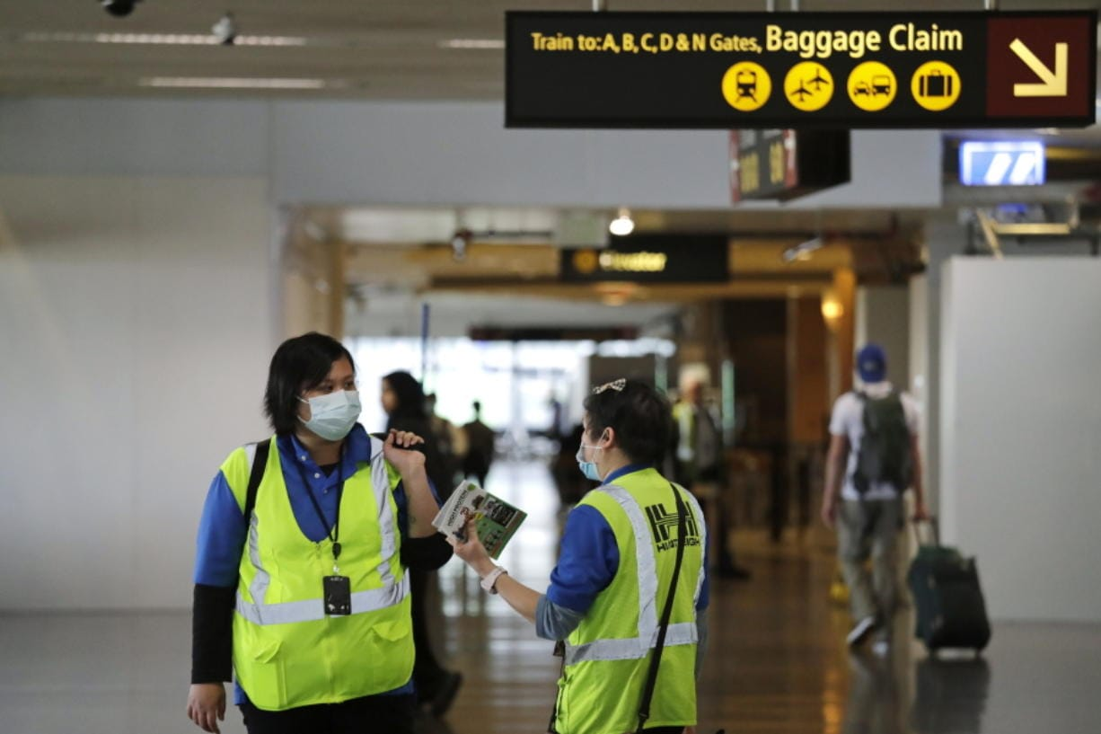 A pair of workers at Seattle-Tacoma International Airport wear masks Tuesday, March 3, 2020, in SeaTac, Wash. Six of the 18 Western Washington residents with the coronavirus have died as health officials rush to test more suspected cases and communities brace for spread of the disease. All confirmed cases of the virus in Washington are in Snohomish and King counties.