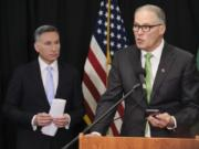 Washington Gov. Jay Inslee reads from an email from his mobile phone as he talks to reporters while King County Executive Dow Constantine listens, Wednesday, March 11, 2020, during a news conference in Seattle. In efforts to slow the spread of the coronavirus, Inslee announced a ban on large public gatherings in three counties in the metro Seattle area.  The vast majority of people recover from the new coronavirus. According to the World  Health Organization, most people recover in about two to six weeks, depending on the severity of the illness.