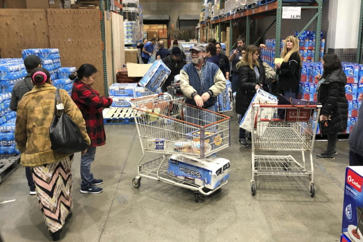 Shoppers wait their turn to pick up toilet paper that had just arrived at a Costco store in Tacoma on March 7. Within minutes, several pallets of toilet paper and paper towels were sold out as people continue to stock up on necessities due to fear of the COVID-19 coronavirus. Similar scenes have occurred at other Costco locations, including in Vancouver. (Ted S. Warren/Associated Press)