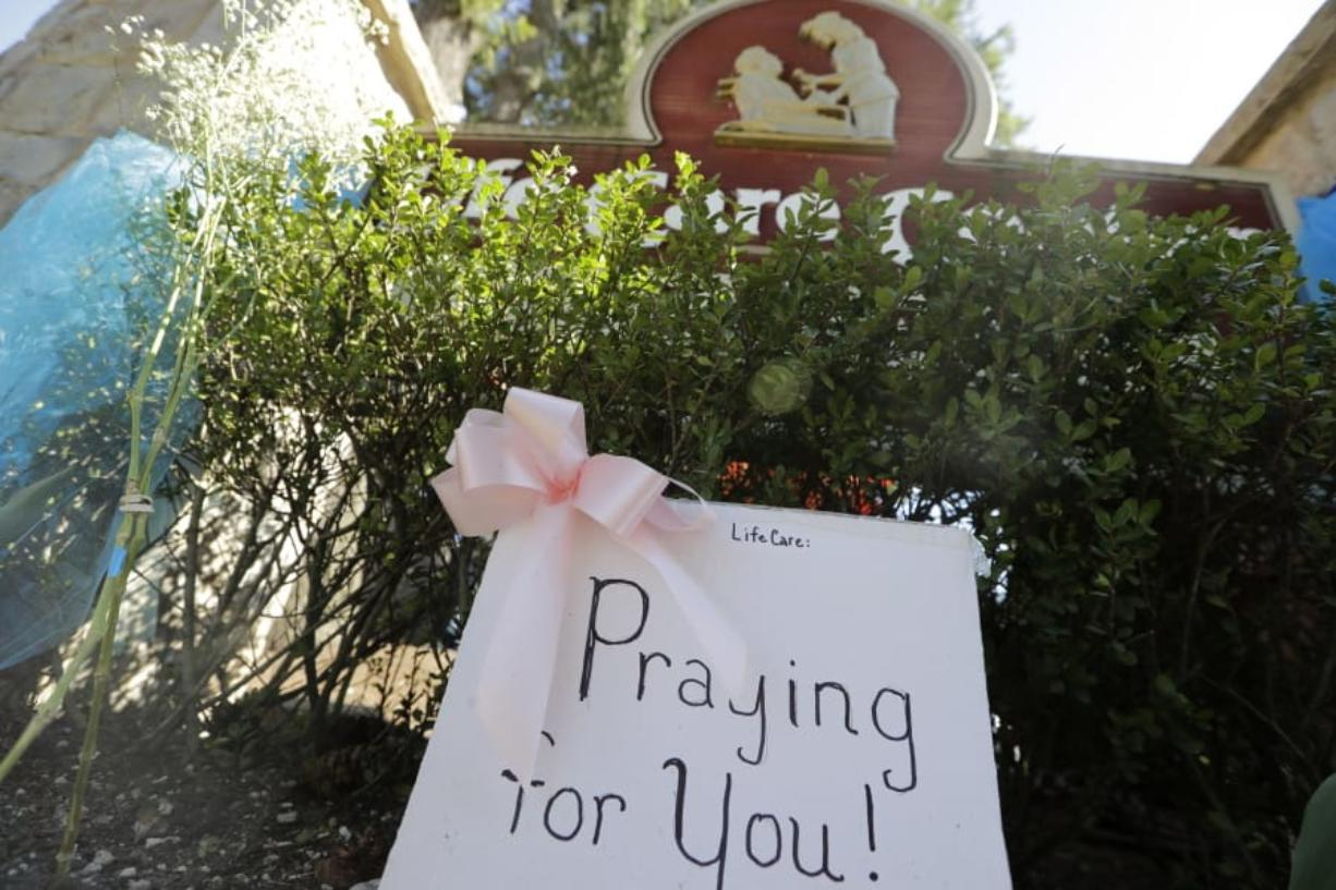 A handmade sign sits against the entry at Life Care Center Monday, March 16, 2020, in Kirkland, Wash., near Seattle. The facility has been the epicenter of the coronavirus outbreak in the state. (AP Photo/Elaine Thompson)