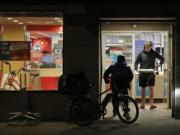A man uses his elbow to open the door as he walks out of a Domino's Pizza restaurant in downtown Seattle as a delivery driver walks in Sunday. Washington Gov. Jay Inslee said Sunday night that he would order all bars, restaurants, entertainment and recreation facilities in the state to temporarily close to fight the spread of the COVID-19 coronavirus. Inslee said that restaurants could continue takeout and delivery services. (Ted S.