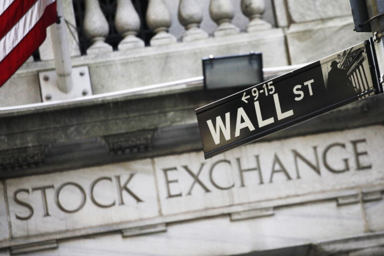 FILE - This July 16, 2013 file photo shows a street sign for Wall Street outside the New York Stock Exchange in New York.  Stocks are opening slightly lower on Wall Street, Tuesday, March 31, 2020, as investors close out a brutal month of March.