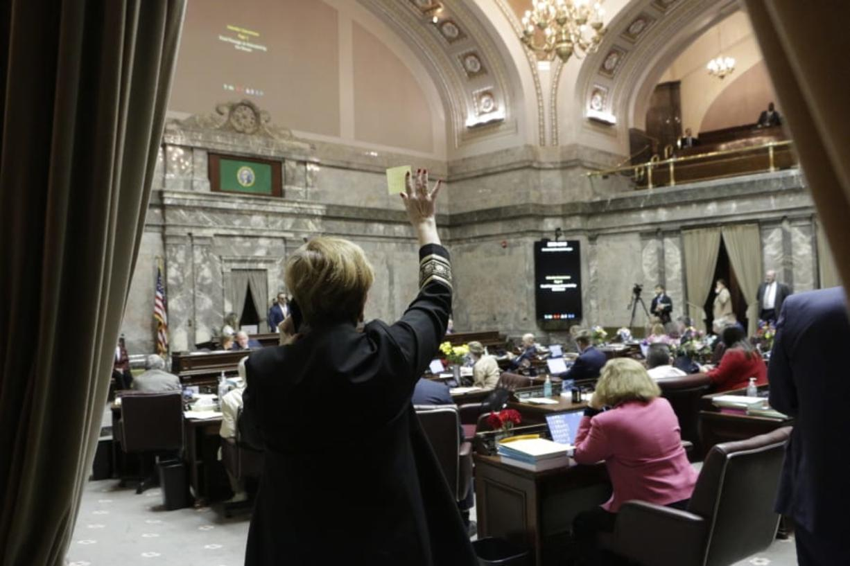 Democratic Sen. Lisa Wellman raises her hand during a vote in the Washington Senate, Thursday, March 12, 2020 in Olympia, Wash. Lawmakers were finishing up their work amid concerns of the state's COVID-19 outbreak. For most people, the new coronavirus causes only mild or moderate symptoms. For some it can cause more severe illness.