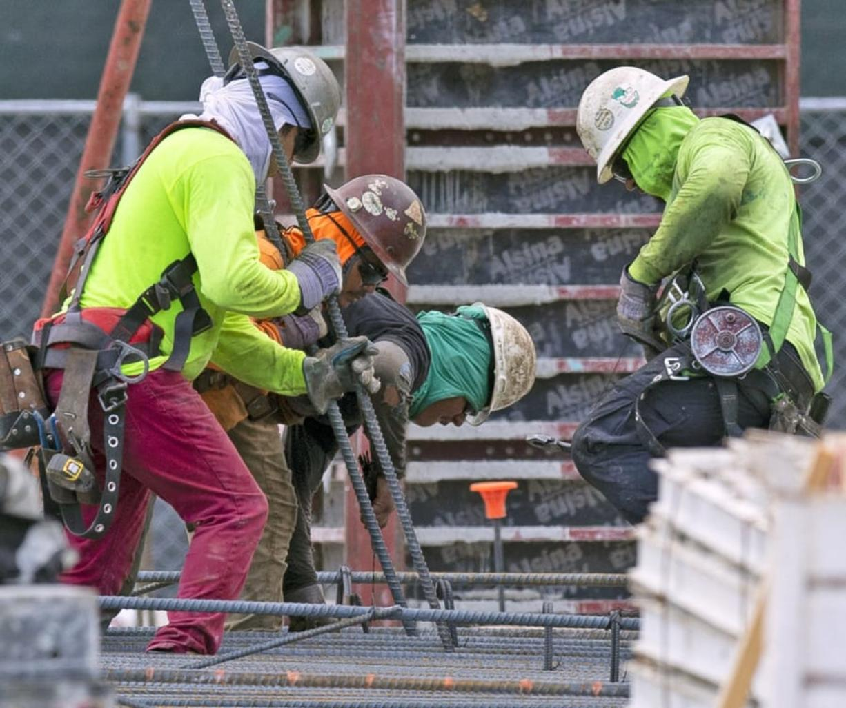 Construction workers labor at the construction site off South Dixie Highway and SW 37th Avenue in Coral Gables, Fla., on March 31, 2020.