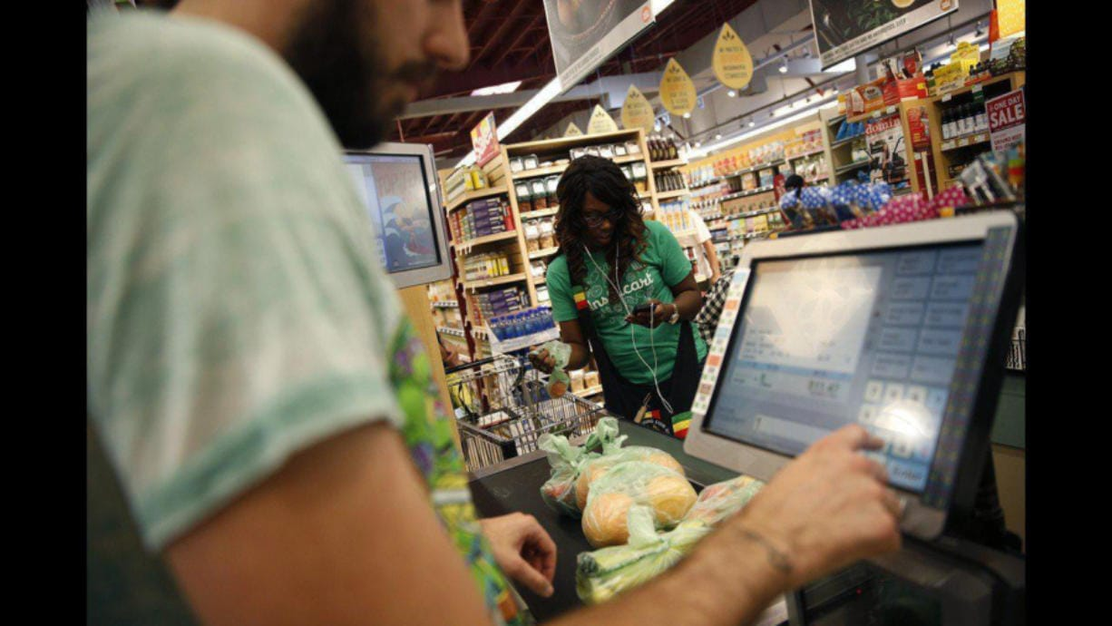 Whole Foods cashier Jason Ellsworth rings up groceries purchased by Instacart shopper Kara Pete. Instacart shoppers and delivery workers went on strike Monday over lack of protection against the coronavirus.