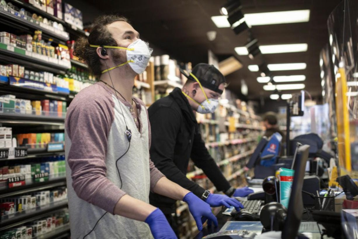Dimitri Miras and Dustin Anderson wear face masks and gloves and stand behind a plastic barrier while working at the Cedar Mill Liquor Store in Portland, on March 26, 2020, amid the coronavirus pandemic and Oregon Gov. Kate Brownu2019s stay-home order.