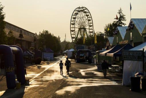 Two volunteers walk through the Clark County Fair before the doors open in 2018.