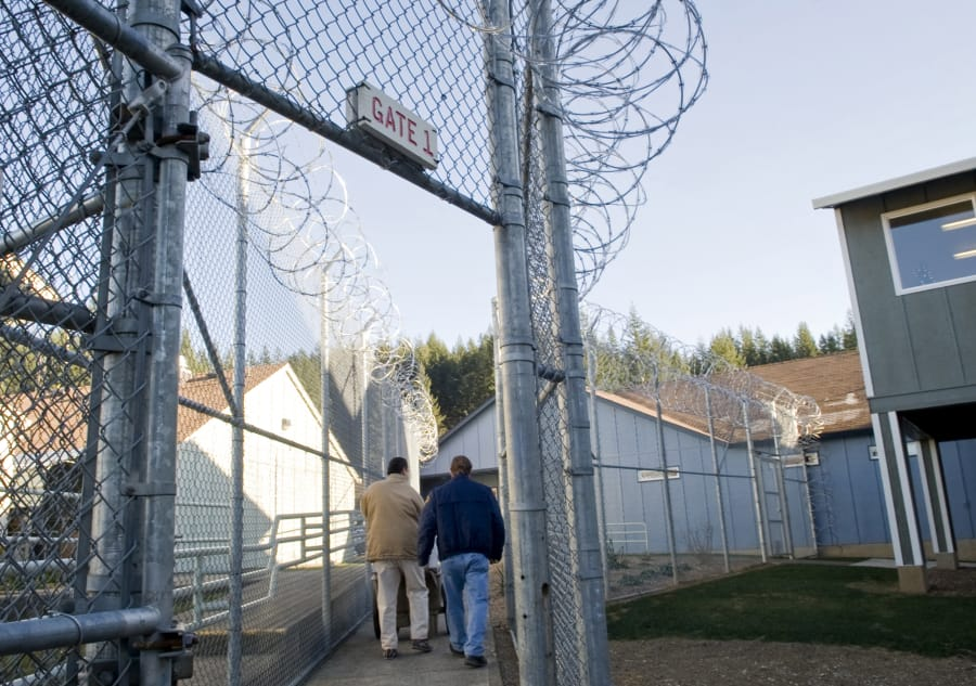 An inmate and guard walk through a gate at Larch Corrections Center in December 2009.