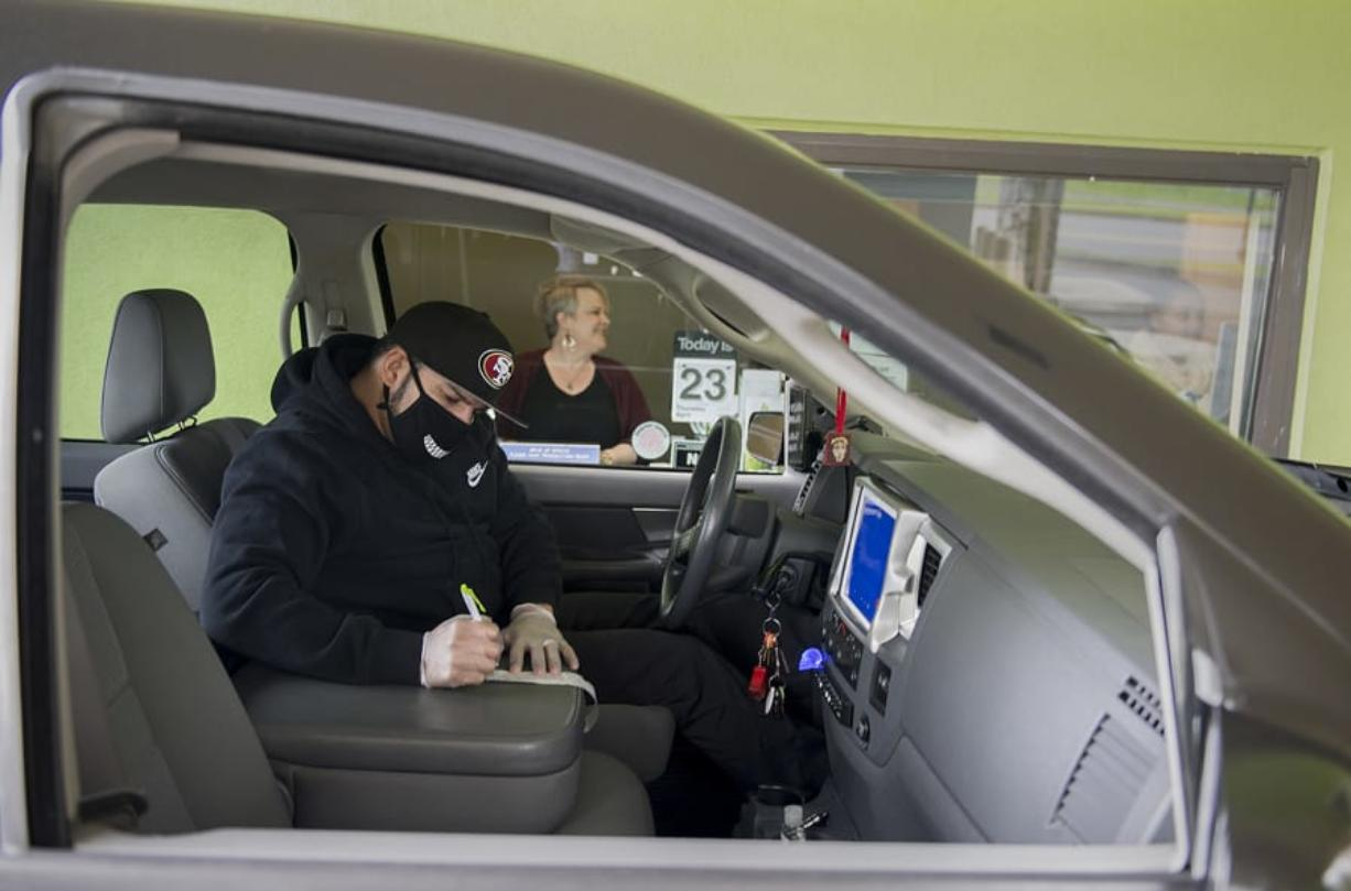 Vancouver resident Ruben Renteria, foreground, checks out his receipt while teller Melissa Engler looks on as he stops by the Cascade Park Columbia Credit Union Branch drive-thru Thursday afternoon. Banks are still allowed to operate during the COVID-19 pandemic, but most are using drive-thru and appointment-only service.