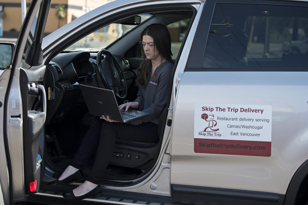 Katie O'Daniel, owner and driver with Skip the Trip Delivery, pauses for a portrait with her laptop in Washougal before making a delivery in Camas.