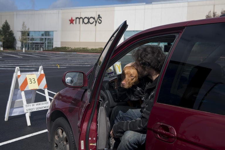 Gerhard Bush-Tschosik of Vancouver shares a kiss with his pit bull mix, Reece, 1, after securing their parking spot at Vancouver Mall on Thursday morning, April 2, 2020. Officials registered car campers vehicles on a first-come, first serve basis starting Thursday. (Amanda Cowan/The Columbian)