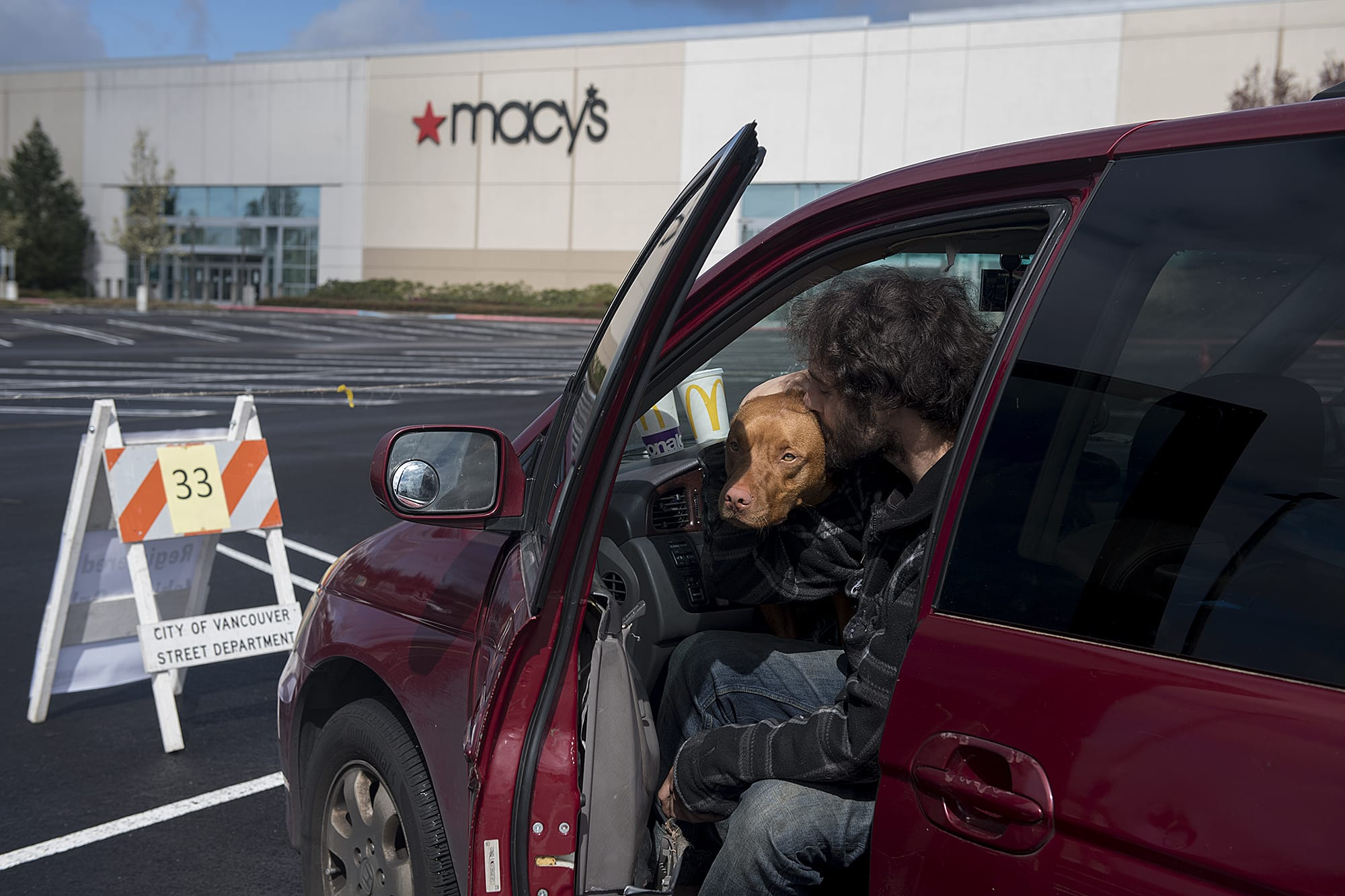 Gerhard Bush-Tschosik of Vancouver shares a kiss with his pit bull mix, Reece, 1, after securing their parking spot at Vancouver Mall on Thursday morning, April 2, 2020. Officials registered car campers vehicles on a first-come, first serve basis starting Thursday.