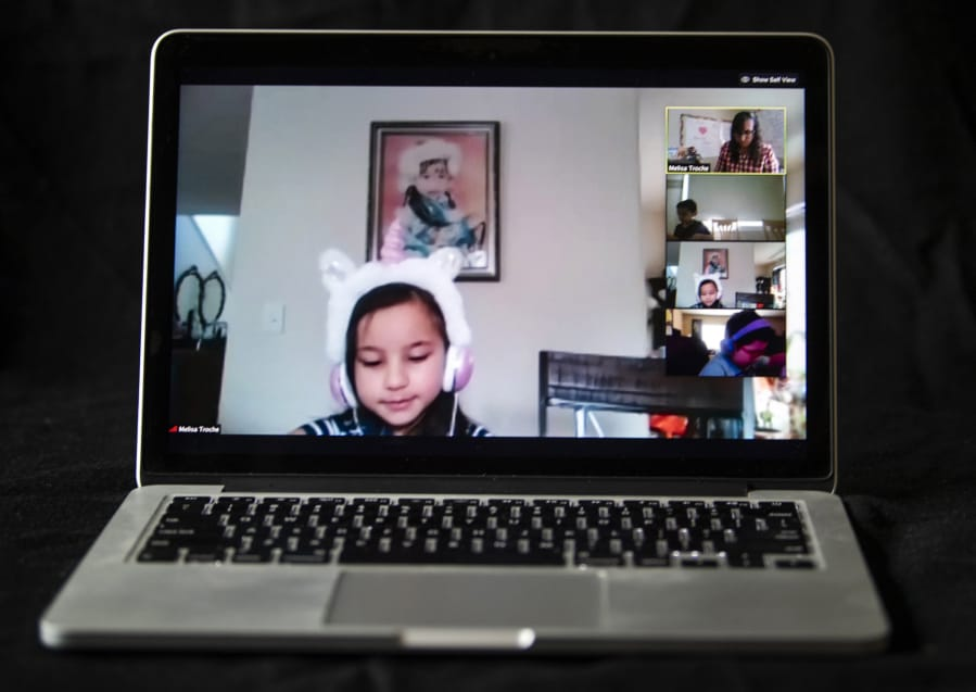 Pioneer Elementary School first-grader Andria Gruetske listens to his teacher, Melisa Troche, as the class joins in on a teleconference call in Vancouver on Monday.
