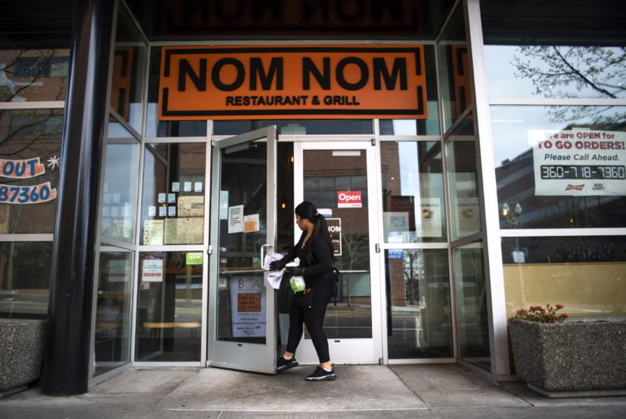 Nom Nom operations manager Sol Contreras wipes down the door handles as she opens up the restaurant at 801 C St. Nom Nom is still open for takeout and delivery orders.
