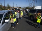 Cars fill the parking lots and line the streets surrounding the Clark County Food Bank to pick up food Tuesday afternoon. The food bank packed boxes and bags filled with food to give away to people in need during the COVID-19 pandemic.