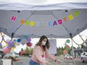 Jessica Mofford cleans a metal basket used to deliver bags of plastic Easter eggs during Activate Church's drive-thru Easter egg hunt in Camas on Saturday morning, April 11, 2020.