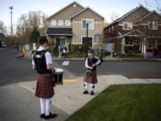 """Drummer Daniel Gillespie, 15, and bagpiper Logan Gillespie, 12, perform a brief concert Wednesday for their Battle Ground neighbors. At far right across the street is Bev Lohrman, a night-shift nurse who cares for COVID-19 patients in the intensive care unit at PeaceHealth Southwest Medical Center. Every time the brothers play her late mother's favorite song, """"Amazing Grace,"""" Lohrman said she hears her mother reassuring her that everything will be OK."""