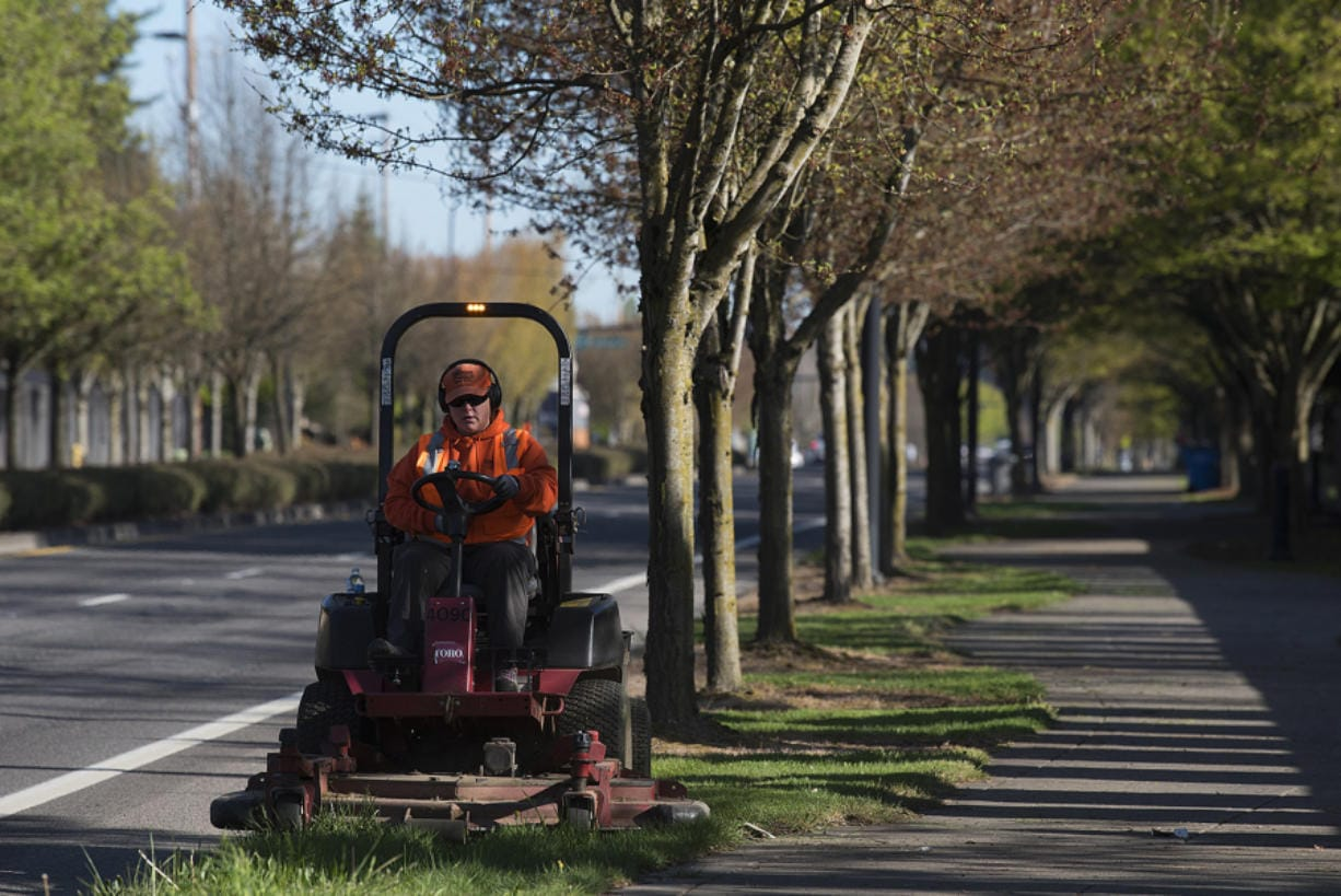 Storme Telford of the Vancouver Public Works department trims grass along Southeast 192nd Avenue on Tuesday morning. Vancouver has resumed some nonemergency public works operations, like mowing and street sweeping. Telford was given a protective mask but said she was not using it because she was away from people.