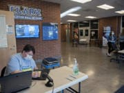 Library staff member Amanda Brown, left, prepares laptops in O'Connell Sports Center for student pickup at Clark College on Monday morning. The college moved almost all its classes online due to shutdown orders connected to the novel coronavirus.