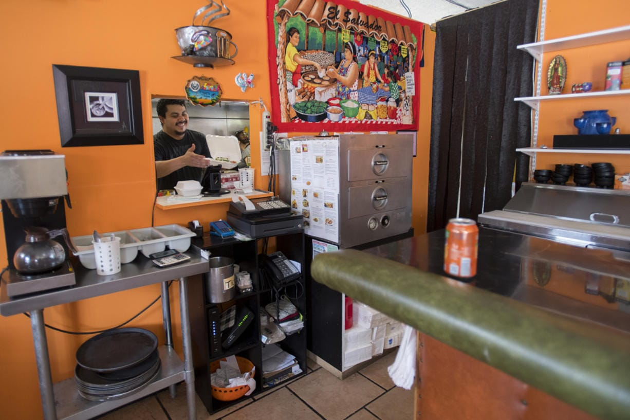 Robert Ayala, one of the owners of Mi Casa Pupuseria, prepares an order during Wednesday's lunch rush. Business has slowed down during the COVID-19 pandemic.