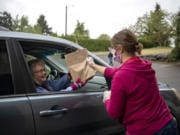 Donna Goff of Vancouver, left, picks up a bag of soup and face masks from Cheri Davis of Woodland on Saturday at Hazel Dell Church of Christ.