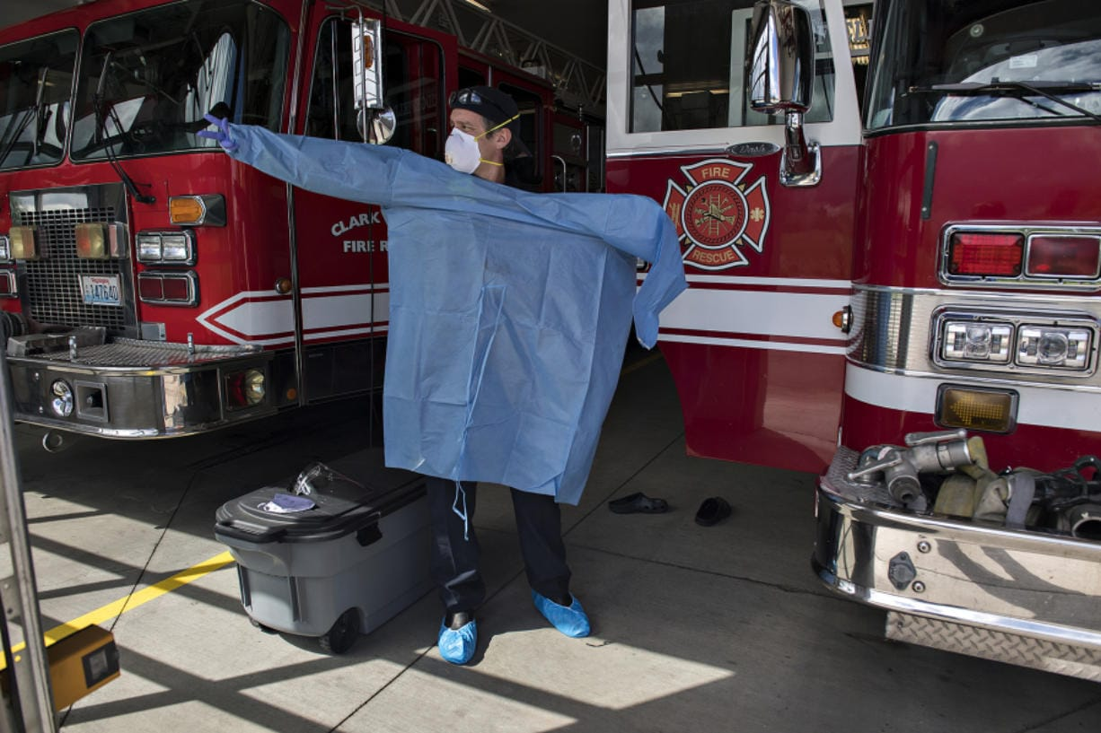 Clark County Fire & Rescue Capt. Blaine Dohman tries on a gown and personal protective equipment at the main station in Ridgefield on Monday. Fire crews with the agency wear the gear when they respond to calls involving people with symptoms associated with COVID-19.