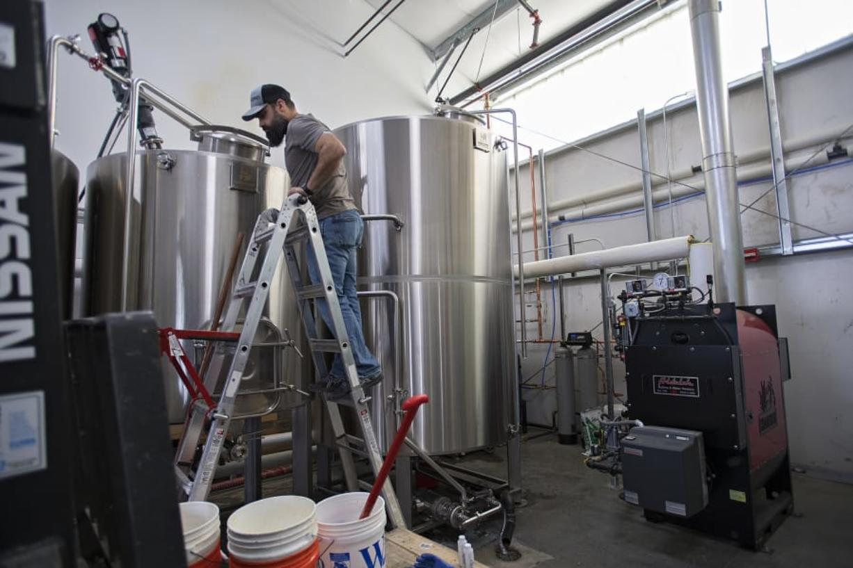 Darin Kyle of Quartz Mountain Distillery keeps an eye on the mash run in preparation for making hand sanitizer to help during the COVID-19 pandemic at his Walnut Grove business.