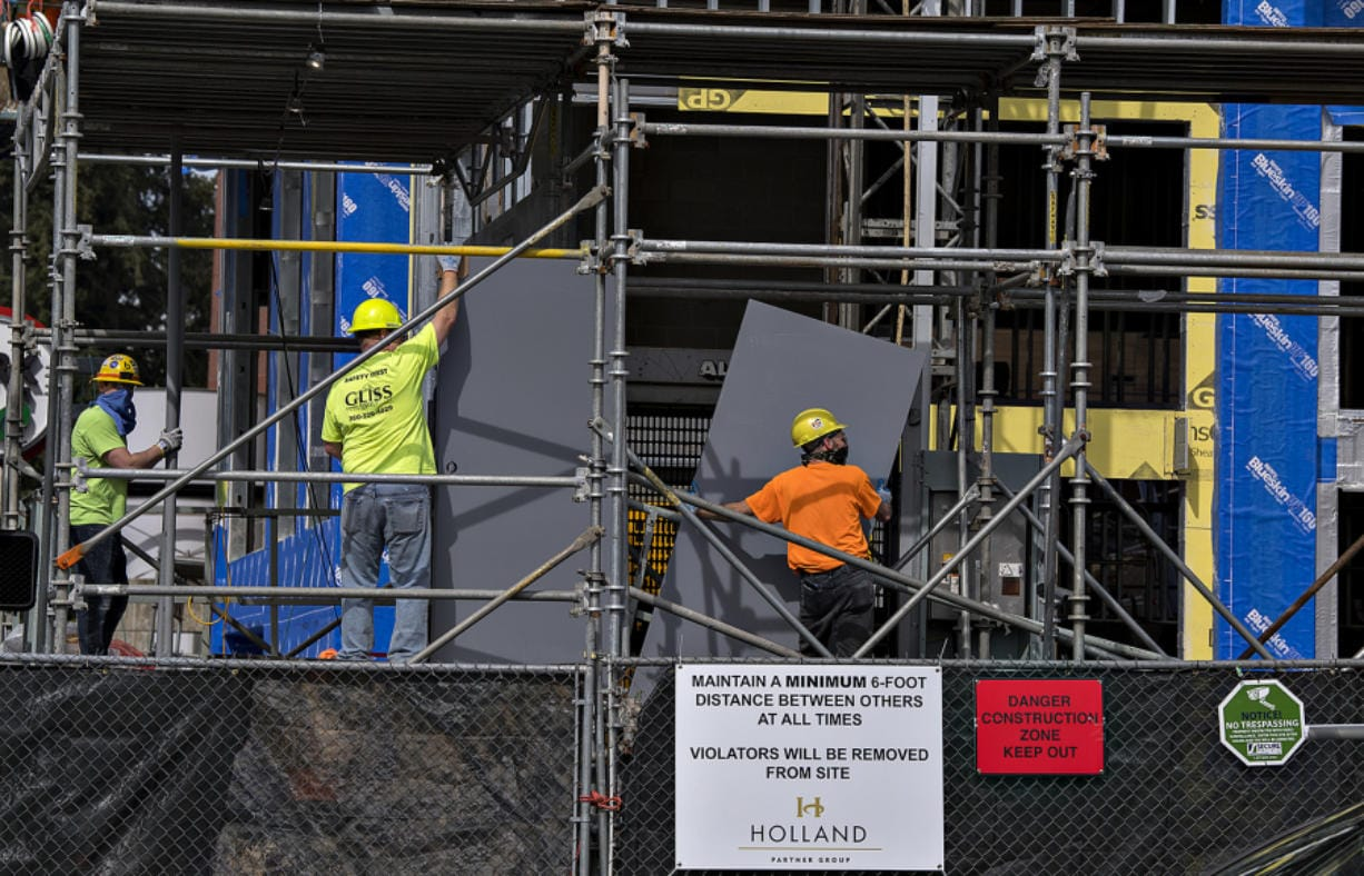 Above, a sign at the Vancouvercenter fourth-tower project site encourages workers to keep a safe distance between each other while working. Health safety signs are one of the new requirements for construction during the COVID-19 pandemic.