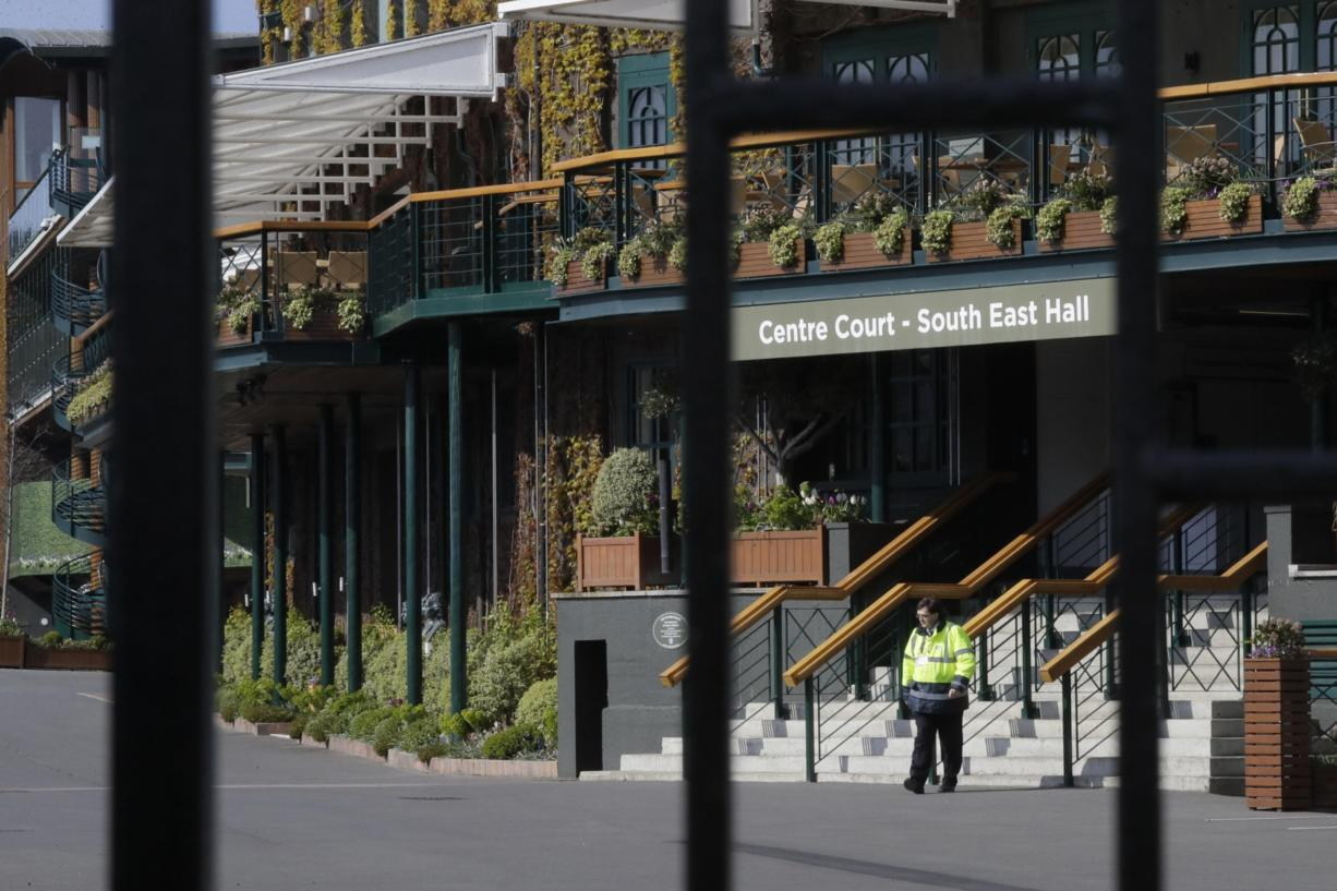 A security guard inside the main gates to Wimbledon as it is announced the the Wimbledon tennis Championships for 2020 has been cancelled due to the coronavirus in London, Wednesday, April 1, 2020.