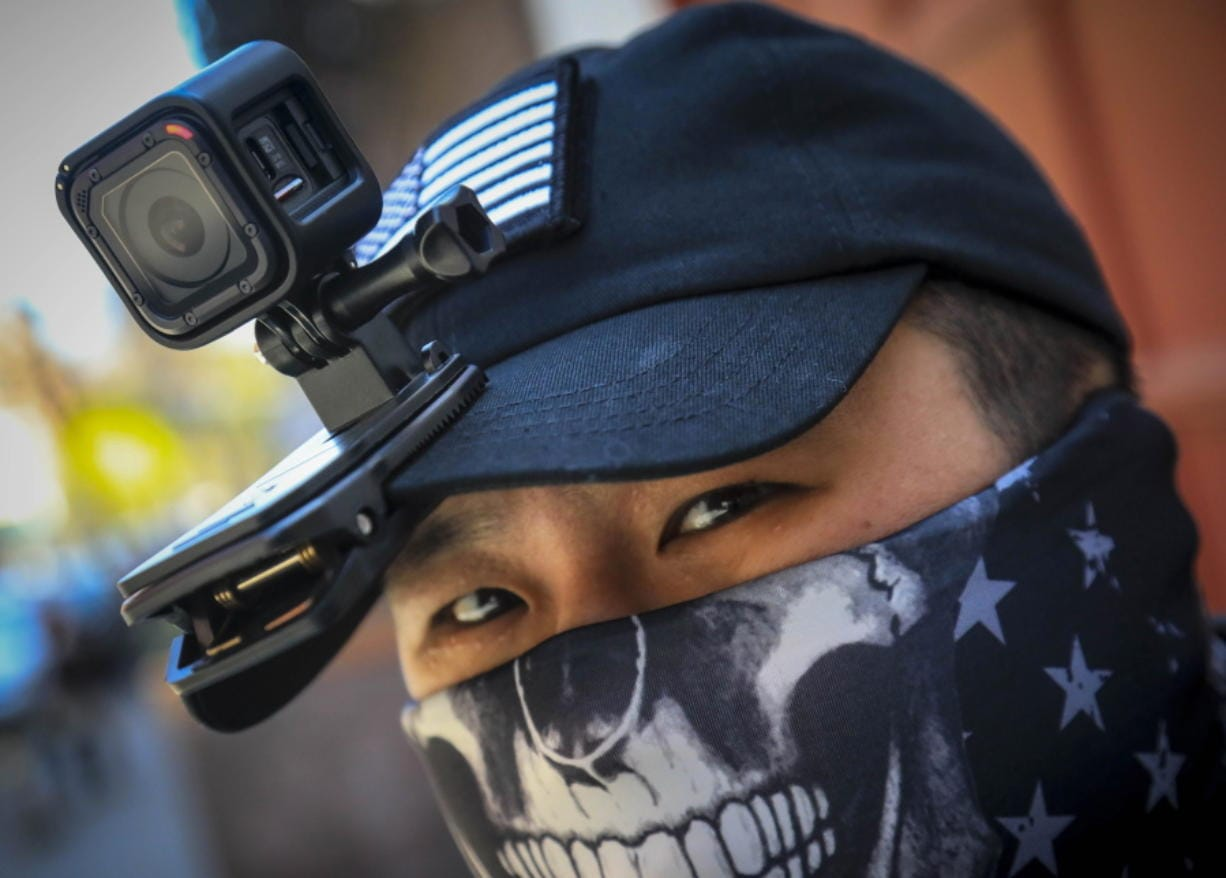 """Eddie Song a Korean American entrepreneur, arrives at his motorcycle storage garage wearing a video camera clipped to his cap and a face mask due to COVID-19, Sunday April 19, 2020, in East Village neighborhood of New York. """"I was assaulted a few months ago by someone who said that corona[virus] was created by Asians,"""" said Song. Since the assault, Song routinely wears cameras and extra padding under his jacket while walking or riding, prepared to record and intervene to stop racist attacks against Asians being blamed for COVID-19."""