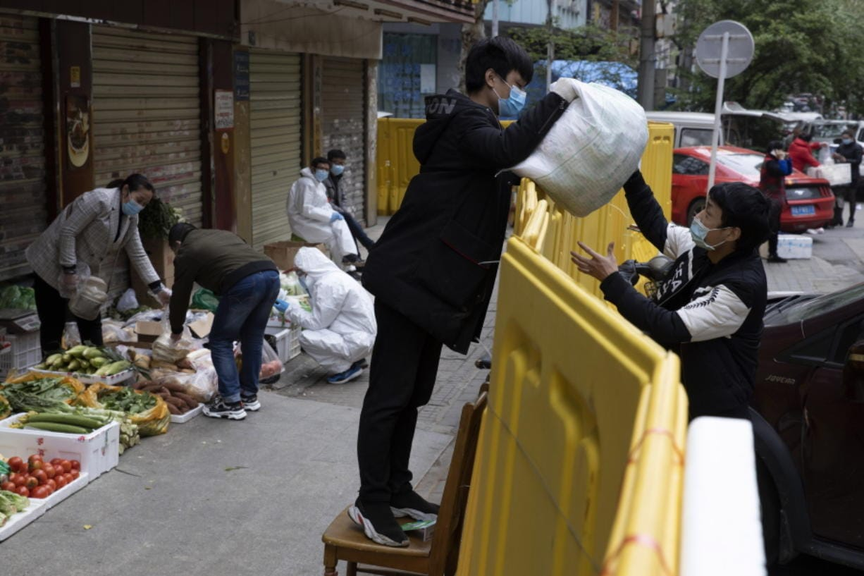 A vendor hands over grocery to another across barriers used to seal off a neighborhood to help curb the spread of the coronavirus in Wuhan, China, Friday, April 3, 2020. Sidewalk vendors wearing face masks and gloves sold pork, tomatoes, carrots and other vegetables to shoppers Friday in the Chinese city where the coronavirus pandemic began as workers prepared for a national memorial this weekend for health workers and others who died in the outbreak.