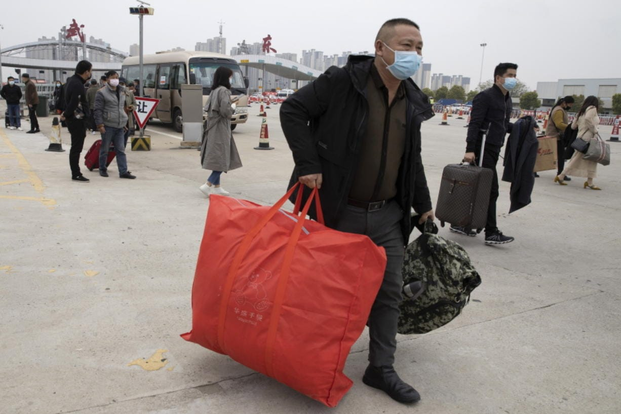 Residents carry their belongings as they walk past a toll booth to enter the city of Wuhan which is still under lockdown due to the coronavirus outbreak but have started allowing some residents to return in central China's Hubei province on Thursday, April 2, 2020.
