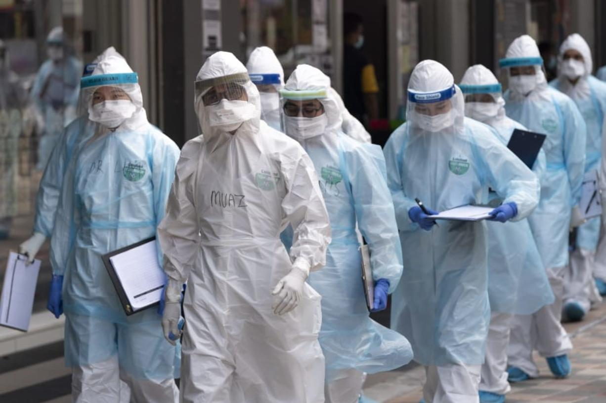 Medical workers in protective suits entering a building under lockdown in downtown Kuala Lumpur, Malaysia, on Tuesday, April 7, 2020. The Malaysian government issued a restricted movement order to the public to help curb the spread of the new coronavirus. The new coronavirus causes mild or moderate symptoms for most people, but for some, especially older adults and people with existing health problems, it can cause more severe illness or death.