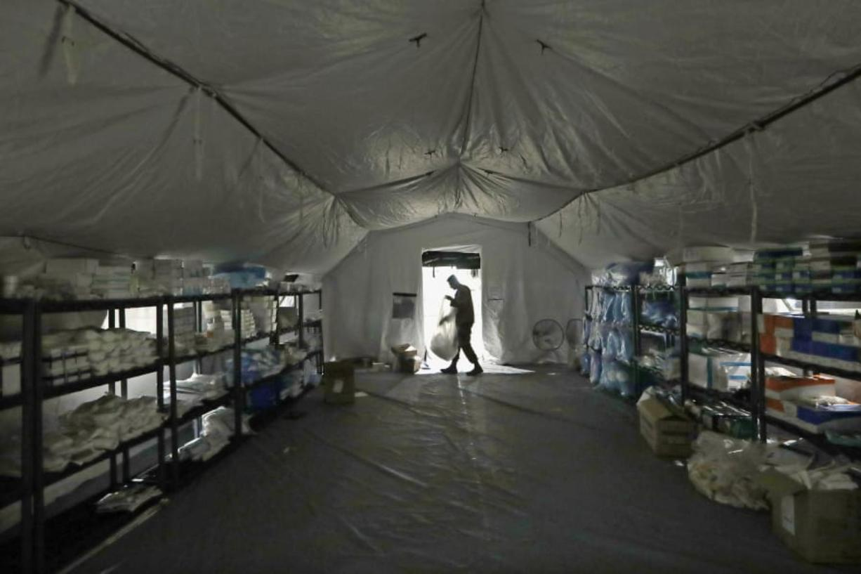 A U.S. Army soldier walks inside a mobile surgical unit being set up by soldiers from Fort Carson, Col., and Joint Base Lewis-McChord (JBLM) as part of a field hospital inside CenturyLink Field Event Center, Tuesday, March 31, 2020, in Seattle. Soldiers from the 627th Army Hospital at Fort Carson, will join soldiers from JBLM to staff the 250-bed hospital to be used for non-COVID-19 cases, allowing local hospitals additional space for patients affected by the coronavirus outbreak. Officials said that the field hospital is expected to be ready to receive patients next week.