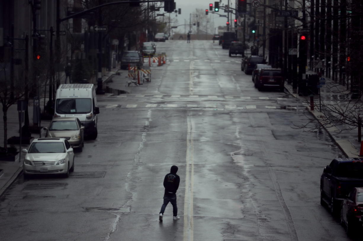 FILE - In this April 3, 2020, file photo a man crosses an empty street in downtown Kansas City, Mo. Americans are increasingly taking preventative measures, including staying away from large crowds and avoiding touching their hands to their faces, amid growing fears of infection with COVID-19, a new poll from The Associated Press-NORC Center for Public Affairs Research found.