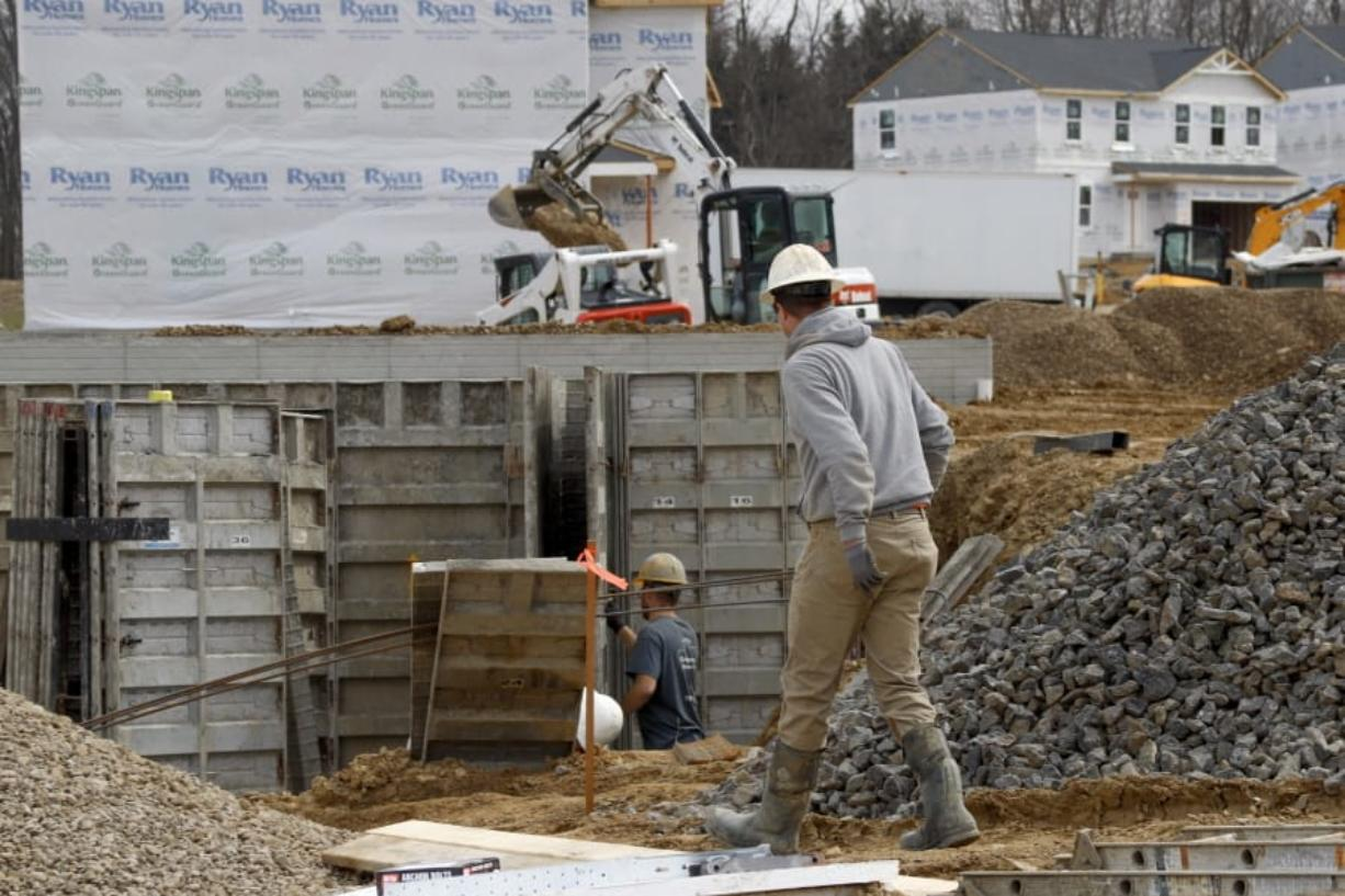 In this March 18 ,2020 photo, construction continues at a housing plan in Zelienople, Pa. Spending on U.S. construction projects fell 1.3% in February with housing and nonresidential construction both showing weakness even before the coronavirus struck with force in the United States. The Commerce Department said the February decline followed a 2.8% rise in construction in January.