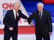 Former Vice President Joe Biden, left, and Sen. Bernie Sanders, I-Vt., right, greet each other before they participate in a Democratic presidential primary debate at CNN Studios in Washington, Sunday, March 15, 2020.
