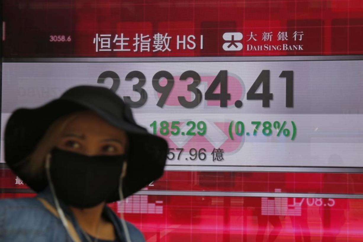 A woman wearing a face mask walks past an electronic board showing Hong Kong share index outside a local bank in Hong Kong, Tuesday, April 7, 2020. Asian shares are rising, echoing the rally on Wall Street fueled by signs of hope that the coronavirus pandemic could be slowing.