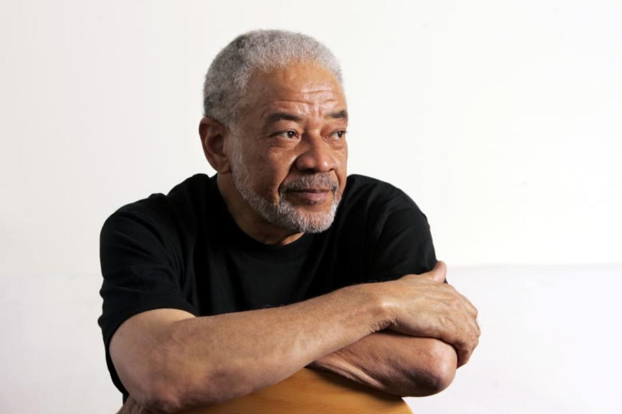 """FILE - In this June 21, 2006 file photo, singer-songwriter Bill Withers poses in his office in Beverly Hills, Calif. Withers, who wrote and sang a string of soulful songs in the 1970s that have stood the test of time, including """"Lean On Me,"""" """"Lovely Day"""" and """"Ain't No Sunshine,"""" died in Los Angeles from heart complications on Monday, March 30, 2020. He was 81."""