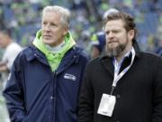 FILE - In this Dec. 30, 2018, file photo, Seattle Seahawks coach Pete Carroll, left, talks with general manager John Schneider before  the team's NFL football game against the Arizona Cardinals in Seattle. There is a clear and obvious need for the Seahawks to address along the defensive line and it happens to be one of the deeper positions of talent in the entire draft. That may be far too simplistic and straightforward for Schneider and Carroll. Schneider is always good for a few surprises in the draft, and more than a couple of trades.