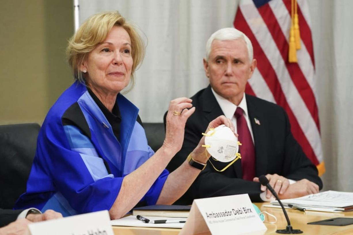"""FILE - In this March 5, 2020, file photo, Dr. Deborah Birx, Ambassador and White House coronavirus response coordinator, holds a 3M N95 mask as she and Vice President Mike Pence visit 3M headquarters in Maplewood, Minn., in a meeting with the company's leaders and Minnesota Gov. Tim Walz to coordinate response to the COVID-19 coronavirus. On Friday, April 3, 2020, the manufacturing giant pushed back against criticism from Trump over production of face masks that are badly needed by American health care workers. 3M said the administration asked it to stop exporting medical-grade masks to Canada and Latin America, which the company said raises """"significant humanitarian implications"""" and will backfire by causing other countries to retaliate against the U.S."""