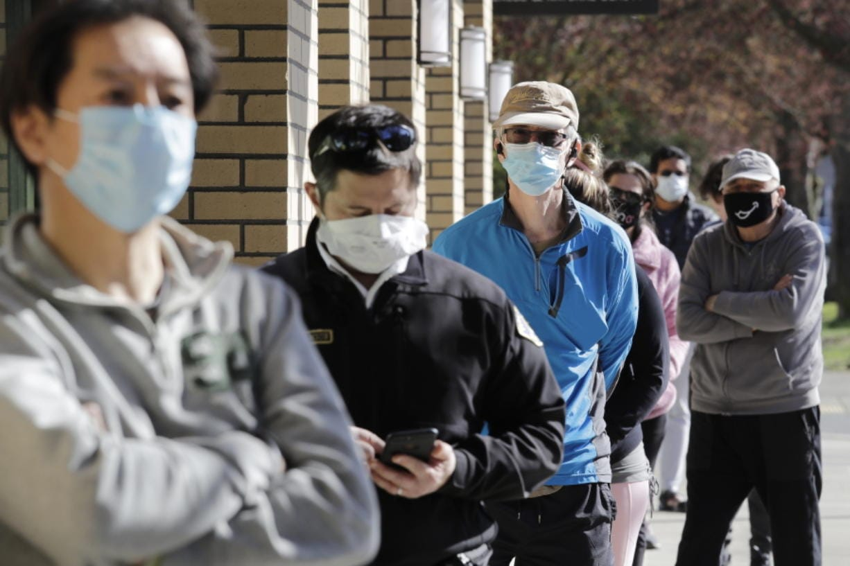 Customers wear a variety of protective masks as they wait some six-feet apart to enter a Trader Joe's store, where the number of customers allowed inside at any one time was limited because of the coronavirus outbreak, Wednesday, April 8, 2020, in Seattle.