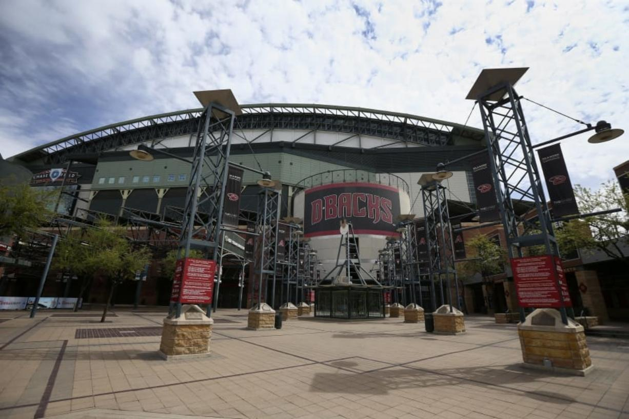 The main entrance in front of Chase Field is devoid of activity in Phoenix. Putting all 30 teams in the Phoenix area this season and playing in empty ballparks was among the ideas discussed Monday, April 6, 2020 during a call among five top officials from MLB and the players' association that was led by Commissioner Rob Manfred, people familiar with the discussion told The Associated Press.  (AP Photo/Ross D.