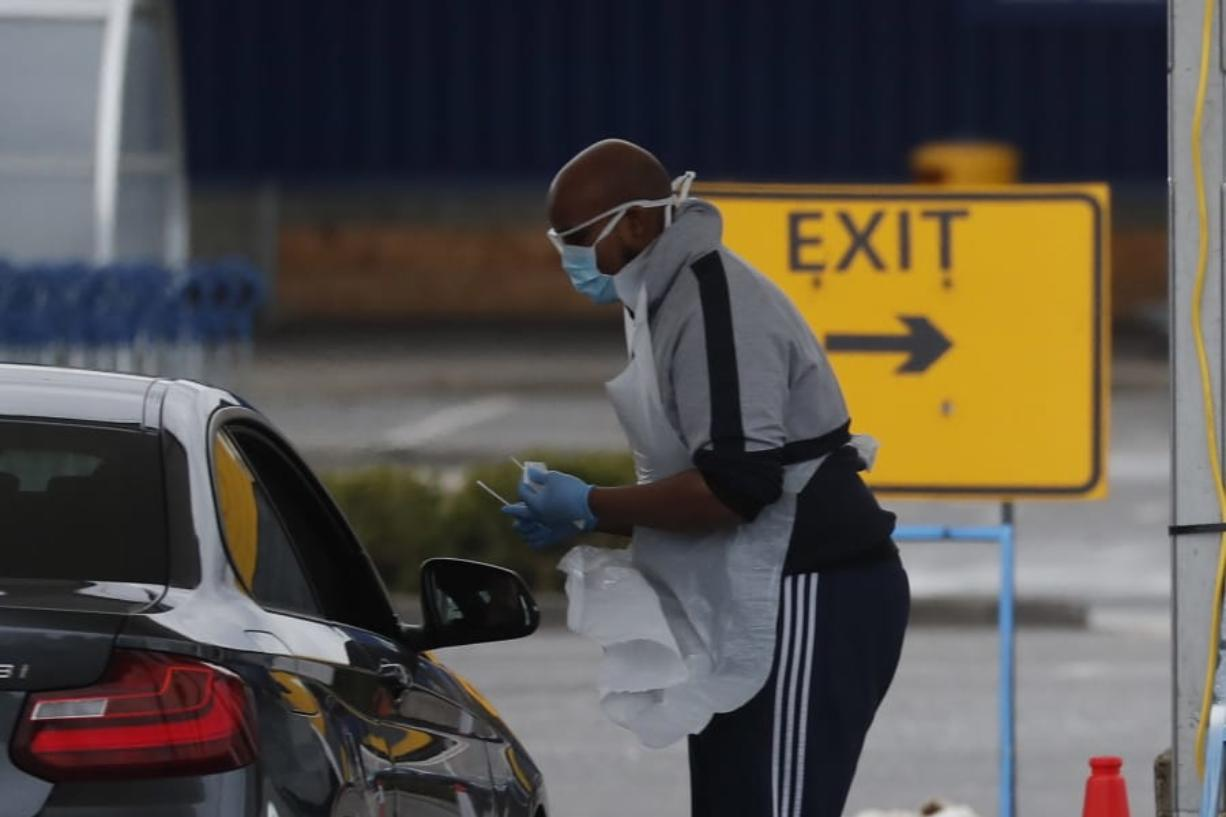 National Health Service staff wait in their cars to take a coronavirus test at a drive through centre in north London, Wednesday, April 1, 2020.