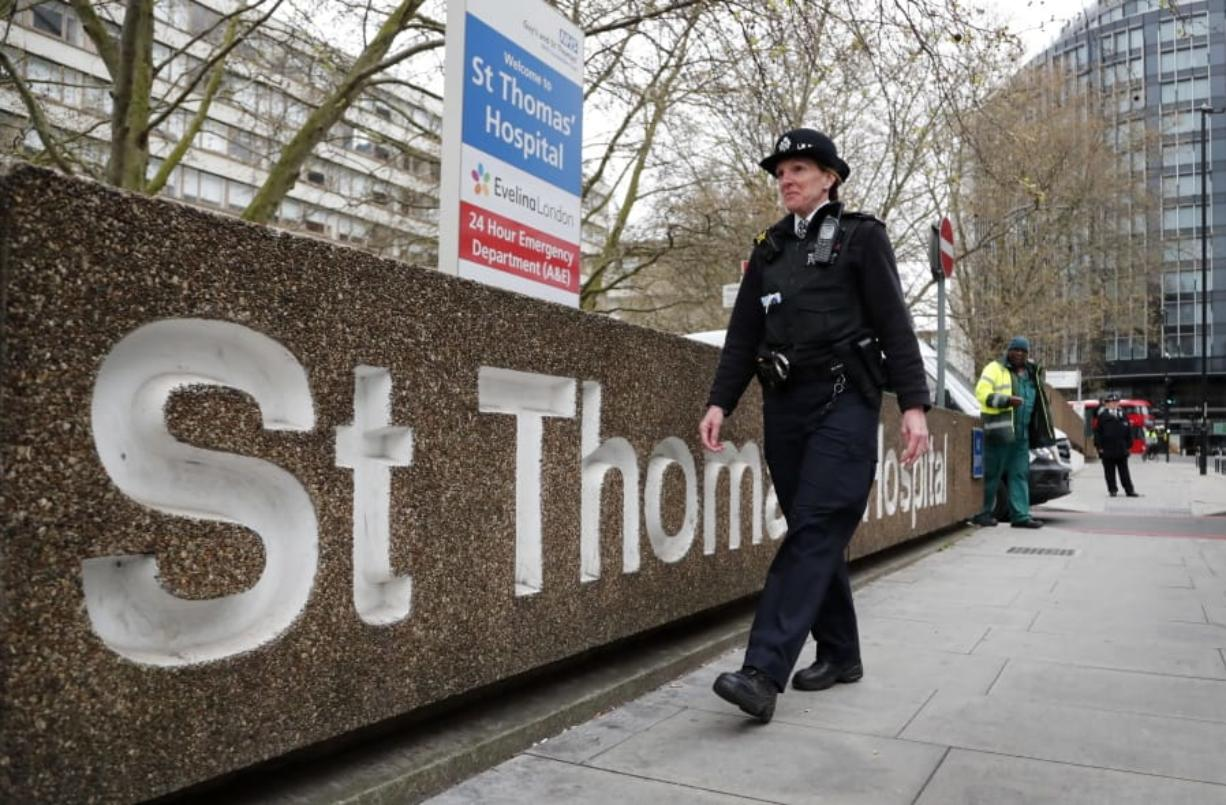 A police officer patrols outside a hospital where it is believed but not confirmed that Britain's Prime Minister Boris Johnson is undergoing tests after suffering from coronavirus symptoms, in London, Monday, April 6, 2020. British Prime Minister Boris Johnson has been admitted to a hospital with the coronavirus. Johnson's office says he is being admitted for tests because he still has symptoms 10 days after testing positive for the virus.
