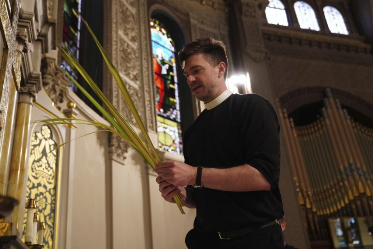 The Rev. Steven Paulikas decorates an altar with palm fronds March 29 for Palm Sunday, which will be commemorated virtually this year, at All Saints' Episcopal Church in the Brooklyn borough of New York.